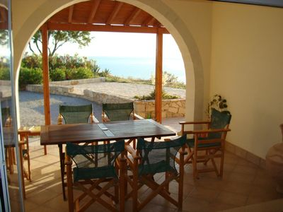 Covered terrace leading off lounge overlooking bay