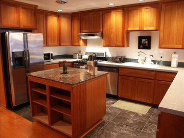 Spacious Kitchen features Custom Cherry Wood Cabinets.