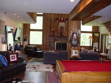 Two story great room with fireplace, pool table and large, flat screen tv.