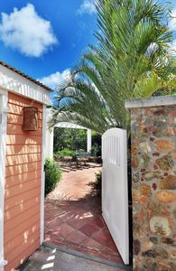 Gated entry to private patio with BBQ and outdoor dining area