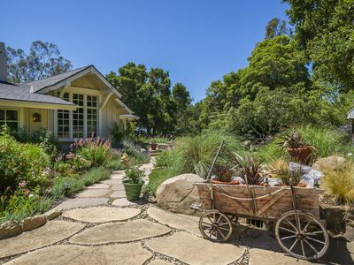 The stone path invites you to explore the gardens that surround this lovely home.