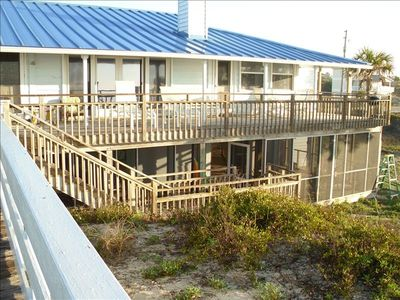 Looking at deck and screened in outdoor room below house from beach boardwalk