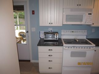 Wellfleet house photo - New kitchen cabinets, tiled floor and granite countertops