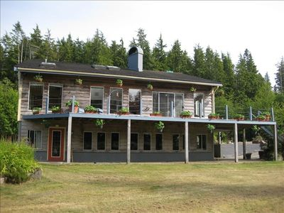 Front view of Bamfield Dragonfly vacation rentals, with large grassy lawn.