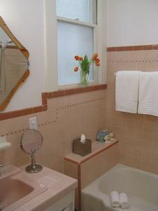 Bathroom with original 1920's tile and art deco mirror.