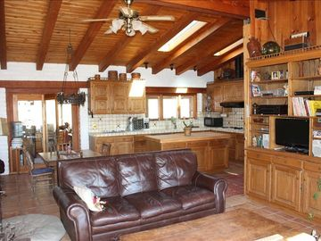 Goleta farmhouse rental - comfortable warm view of living room looking into kitchen, flat screen tv.