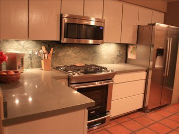 Kitchen with Electrolux stainless and stone counter tops