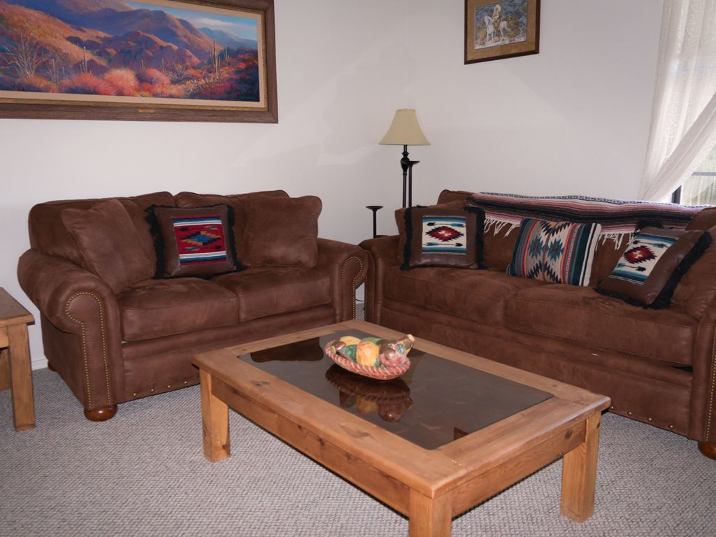 Living room with queen sofabed, loveseat and TV hutch.