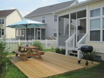 Backyard with Ground Level Deck, Grill, and Picnic Table