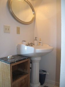 Sink from shower doorway.  Note elegant pedestal sink and stone-top cabinet.