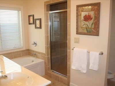 The large master bathroom offers soaking tub and tile shower.