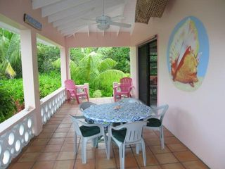 Covered verandah offers large round dining table that seats 6+ persons. - Spanish Wells villa vacation rental photo
