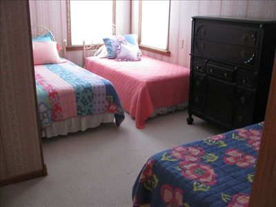 2nd Bedroom has 3 single beds with a view of the lake and walkin closet.