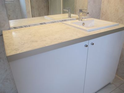 Marble vanity around sink. Bathroom includes both a shower and bathtub!