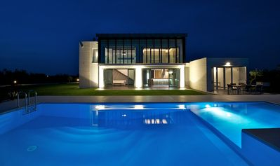 Modern villa with swimming pool surrounded by greenery