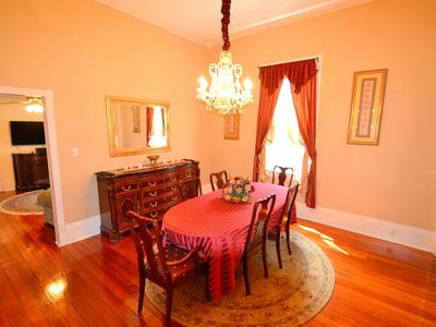 Large, beautiful dining room, with wood floors, a buffet and chandelier.