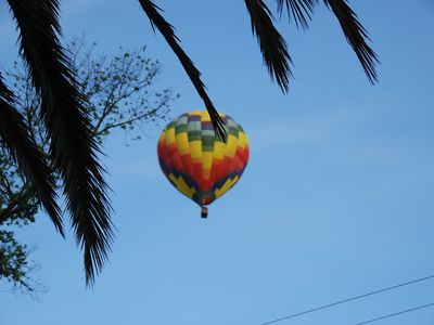 View from the front porch of a hot air balloon floating by.