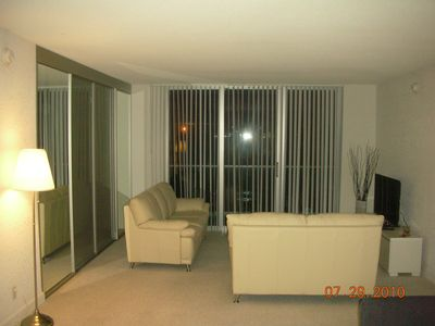 Living room with leather sofas, LCD TV out to balcony
