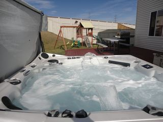Calgary house photo - This hot tub is entertainment for both kids and adults.