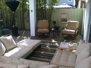 Outdoor sectional, lounge chairs, outdoor heater. All under outdoor patio cover