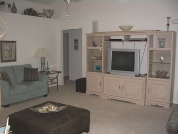 Other half of living room with entertainment center, cable TV, DVD player, books