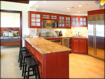 The kitchen with top end stainless steel appliances and travertine granite