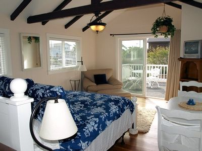 Upstairs king bed and sunny deck with TV/DVD player and view of the surf