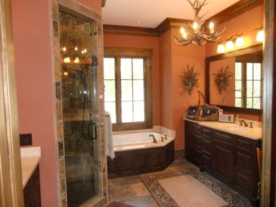 Master bath with stone shower, jetted tub and his and her vanities.