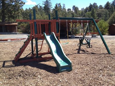 Swing set with rock climbing wall, slide, 3 swings and rope ladder.