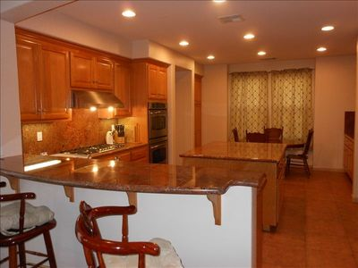 Large kitchen with granite countertops, Island, 2 ovens, dishwasher & gas stove.