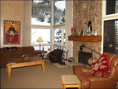 Living room with stone fireplace and view of slopes
