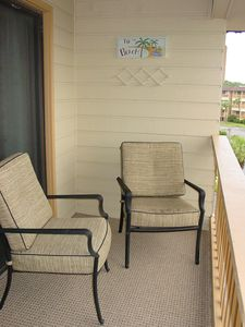 Balcony chairs for relaxing and enjoy the ocean view. Round table on balcony.