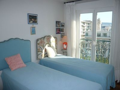 Another bedroom equipped with twin beds, access to a balcony