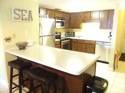 Remodeled kitchen has maple cabinets, SS appliances & solid surface countertop