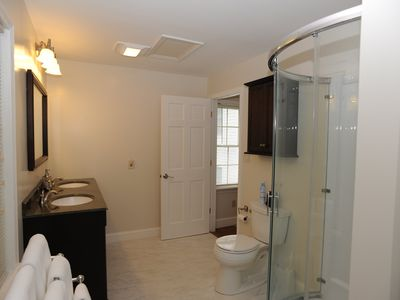 Bathroom with new glass shower, cabinets and vanity with granite counter top.