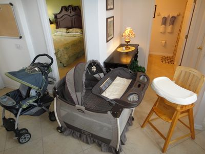 Welcoming Foyer with baby gear on display, high chair, stroller and pack n play.