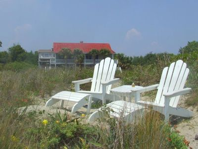 Adirondack chairs atop dunes and next to shore