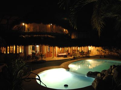 Pool and back of house shown in the evening.