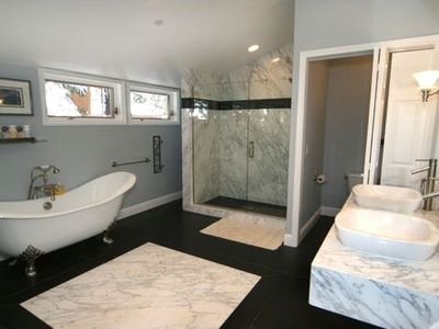Master bathroom with soaking tub, large shower, and his and hers sinks