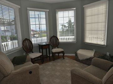 sitting room with comfortable recliners, game table and ocean views