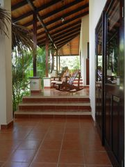 Nosara house photo - The outdoor porch & walkway to the cabana suites with rocking chairs