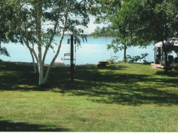 Easy access to the dock and sand beach, campfire circle and screened gazebo.
