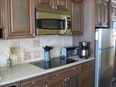 Kitchen close up shows cook top and full size convection\microwave oven