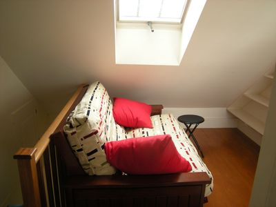 Futon in 3rd floor alcove with window overlooking garden and town.