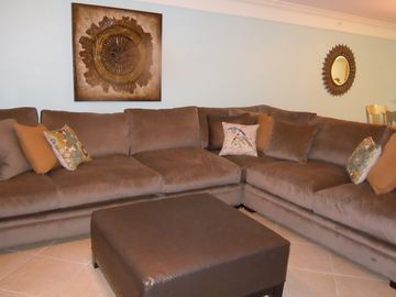 "Large sectional in the Living Room with 60"" Flat screen TV."