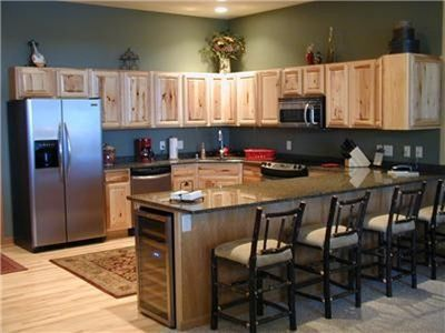 Gourmet kitchen w/island seating and wine fridge.
