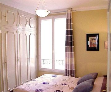 The peaceful bedroom is a cheerful relaxing retreat from a busy day in Paris.