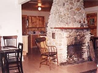 Friendship cottage rental - Kitchen beyond fireplace; living area to the right