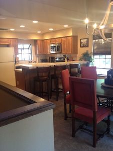 Kitchen with new appliances, and breakfast bar with four swivel stools.