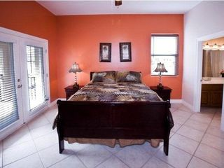 "South Padre Island condo photo - master bedroom with doors to deck area"" now has a new red bed spred"""